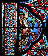Two apostles, one holding a palm frond, possibly St John, to the left of the scene of the apostles carrying the coffin of Mary, from the Funeral of Mary in the Glorification of the Virgin stained glass window, in the nave of Chartres Cathedral, Eure-et-Loir, France. This window depicts the end of the Virgin's life on earth, her dormition and assumption, as told in the apocryphal text the Golden Legend of 1260. Chartres cathedral was built 1194-1250 and is a fine example of Gothic architecture. Most of its windows date from 1205-40 although a few earlier 12th century examples are also intact. It was declared a UNESCO World Heritage Site in 1979. Picture by Manuel Cohen