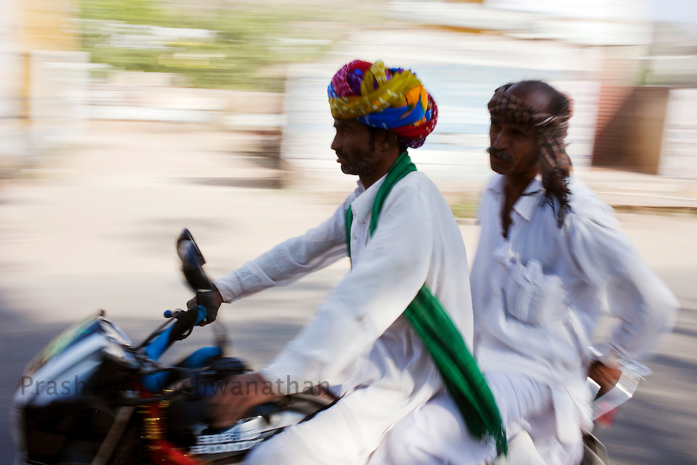 Traditionally clad men drive near the fair grounds in Pushkar, India, November 6, 2011.  Photographer: Prashanth Vishwanathan