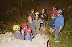 Group of teenagers on school trip preparing to explore cave,