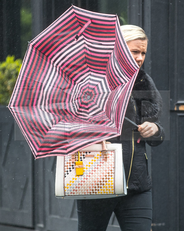© Licensed to London News Pictures. 12/04/2017. Manchester, UK. A woman in the Spinningfields office district of Manchester battles against bitter winds and icy rain , which inverts umbrellas , during a sudden squall in Manchester City Centre . Photo credit: Joel Goodman/LNP
