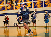 Nick Van Bennekum works on drills with the Lacrosse team in the Gilford High School gym on Friday afternoon.  (Karen Bobotas/for the Laconia Daily Sun)