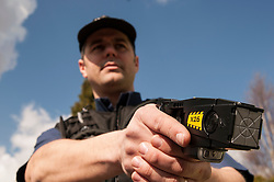 Armed police officer with a taser gun UK