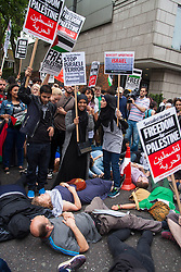 London, July 5th 2014. Demonstrators hold a die-in on Kensington High Street as hundreds protest near the Israeli embassy in London against the ongoing occupation and the west's support of Israel's collective punishment of Palestinians