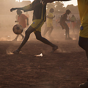 "Amazones team players are training in the  district of Bamako called Bacodjikoronì, that means ""across the river"". The afternoon is very hot, clouds of dust winding girls dribbling, stop, backheel."