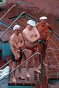 Three men stand at the thermal poolside wearing hygienic hats in Budapest's famous Széchenyi thermal bath. ..Having bathed in thermal waters that are piped through this health resort in the middle of the capital city, the men wear swimming costumes in the warm summer morning where hundreds flock to. Budapest is especially known for its spas just as Germany is. The Széchenyi Medicinal Bath  (Széchenyi-gyógyfürd?) is the largest medicinal bath in Europe. Its water is supplied by two thermal springs, their temperature is 74°C/165°F and 77°C/171°F, respectively. The bath can be found in the City Park, and was built in 1913 in Neo-baroque style to the design of Gy?z? Czigler.