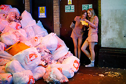 © Licensed to London News Pictures. 01/01/2017. London, UK. Revellers eat take away food next to rubbish bags as revellers celebrate the New Year in central London during the first hours of 2017 on January 1. Photo credit: Tolga Akmen/LNP