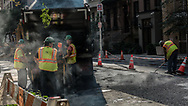 Workmen spreading hot asphalt during another steamy autumn day in New York, Sept. 25, 2017