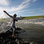 Ashraf Rashad casts his net into the shallow waters of the Red Rock spillway, where roaring waters pour through the dam and into the Des Moines River.  A culture of fishing, recreation and wildlife has sprung from Iowa's largest lake since it's inception in 1969. photo by david peterson