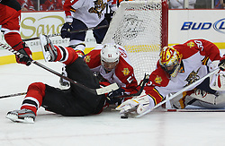 Feb 11; Newark, NJ, USA; Florida Panthers defenseman Brian Campbell (51) pulls down New Jersey Devils right wing Petr Sykora (15) while Florida Panthers goalie Scott Clemmensen (30) reaches for the loose puck during the second period at the Prudential Center.