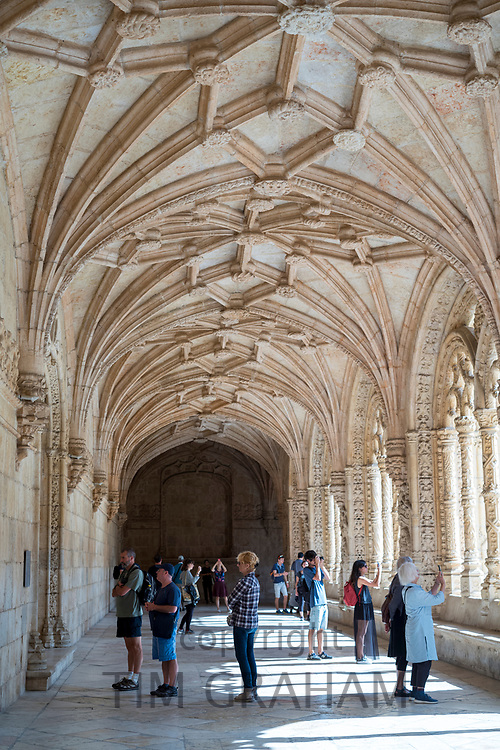 Tourists taking photographs in cloisters of famous Monastery of Jeronimos - Mosteiro  dos Jeronimos in Lisbon, Portugal