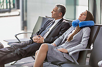 Mature businessman and young attractive businesswoman sleeping while waiting for boarding in their gate at airport