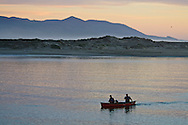 Couple in canoe with pet dog paddle in the calm waters of Morro Bay, California
