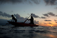 Father and son paddle through a lagoon at sunset. Rah Lava Island, Torba Province, Vanuatu