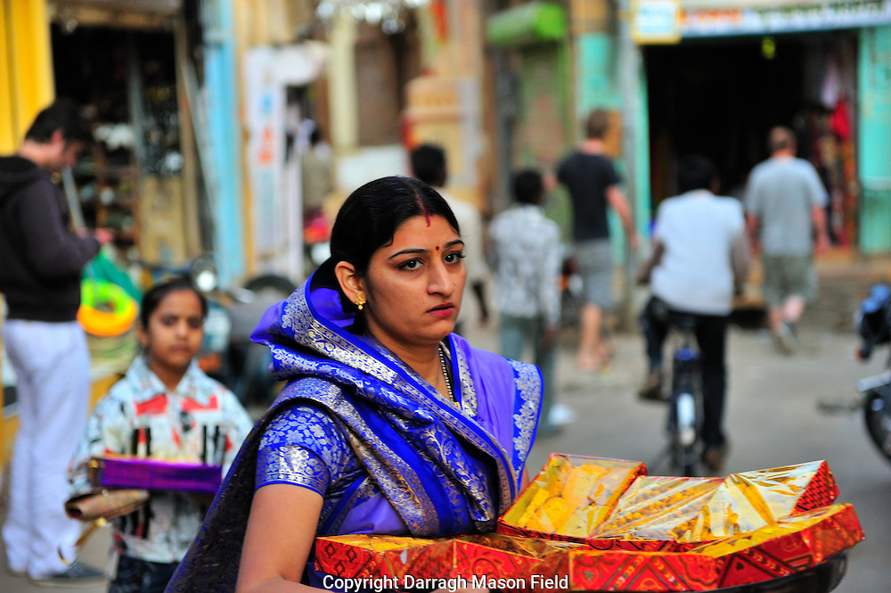 Woman carrying food gifts for a wedding through the streets of Jaisalmer