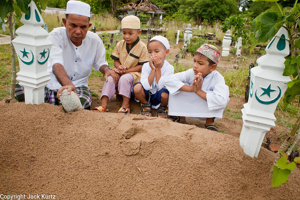 "Sept. 27, 2009 -- PATTANI, THAILAND: Thai Muslim men pray over the graves of family members in the Perkuboran To'Ayah Cemetery in Pattani, Thailand. Thailand's three southern most provinces; Yala, Pattani and Narathiwat are often called ""restive"" and a decades long Muslim insurgency has gained traction recently. Nearly 4,000 people have been killed since 2004. The three southern provinces are under emergency control and there are more than 60,000 Thai military, police and paramilitary militia forces trying to keep the peace battling insurgents who favor car bombs and assassination.   Photo by Jack Kurtz / ZUMA Press"
