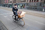 In Amsterdam fietst een man met bloemen in het mandje voorop de fiets door de Vijzelstraat.<br /> <br /> In Amsterdam a man cycles with flowers in a basket at the Vijzelstraat.
