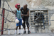 Jorge Donatien, former boxer and trianer,  with a little boxur before a training match on the ring of the gimnasio de boxeo Ninos de Cuba<br /> <br /> <br /> The Cuban boxing has a centennial long prestigious history written by exceptional champions, artists of the ring, whose legendary exploits , continue to live in the stories of fans. In 1962 Cuba had abolished professionalism in sports. Two years ago, driven by economic interests and attempt to stop the bleeding of athletes on the run from the island, sports authorities have announced participation in world boxing championship, the World Series of Boxing (WSB), which are not however a professional circuit because they remain part of the Olympic boxing. Thanks to a law passed a few years ago, with new economic conditions for the Cuban athletes, now, in addition to the contributions they receive from the state, the Cuban boxers will earn from their sport, 80% of the proceeds from participation in international sporting events.<br /> Meanwhile two years ago, in a small corner of Centro Habana, two blocks from the Capitolio and the square of big international hotels such as Telegraph and England, between the peeling walls of two buildings, in the space left by a collapsed building,<br /> thanks also the association Italian Malaika (Angel in swahili), there is a gymnasium de Boxeo, a gym of wooden planks recycled for the children of Centro Habana. In this neighborhood gym the talent and enthusiasm of dozens of children between 7 and<br /> 20 years is concentrated: Los Ninos de Cuba. Every day from 5 pm until late at night they chasing their dreams of success, with ethics, rigor and commitment, The facilities are not enough for everyone. Gloves and shoes alternate in the hands and feet of small boxeadores, which in turn &ldquo;peleano&rdquo; on the makeshift ring waiting to make the leap to the Rafael Trejo, another Boxing Gymnasium, in the heart of Havana Vieja, to participate in provincial and then national champion