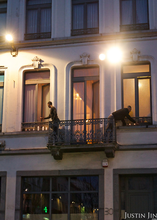 The brother (Left) of Paris attack suspect Saleh Abdelslam lights candles at their apartment terrace in Brussels' Molenbeek neighbourhood, to join participants (both white and Muslim) to demonstrate solidarity with victims of Paris attack. The man on the right is not identifiable.
