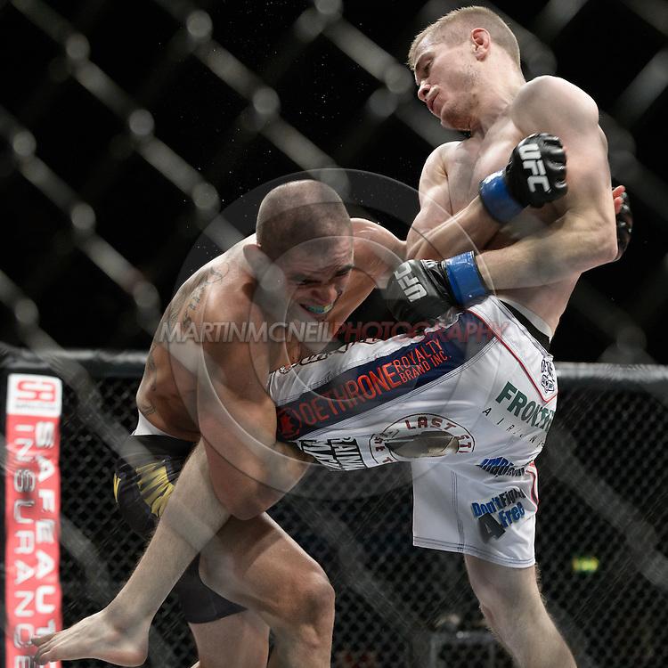 "LONDON, ENGLAND, FEBRUARY 16, 2013: Renan Barao (L) grabs onto Michael McDonald's leg during ""UFC on Fuel TV 7: Barao vs. McDonald"" inside Wembley Arena in Wembley, London on Saturday, February 16, 2013 (© Martin McNeil)"