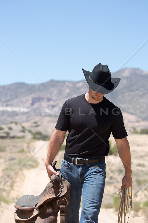 cowboy walking with a saddle in his hand