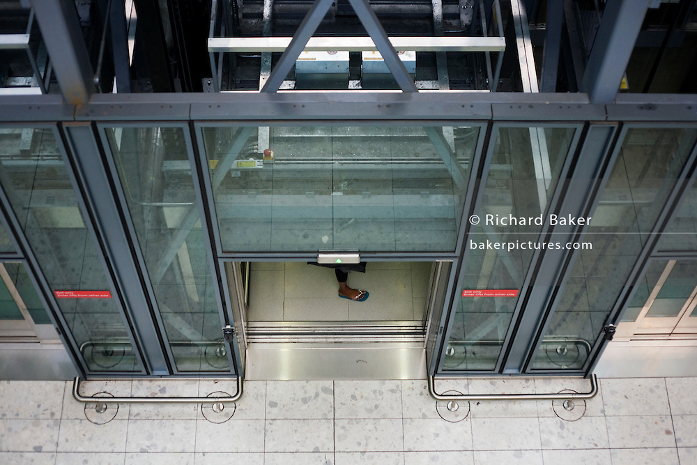 Heathrow Express lift passenger's foot and architecture at Heathrow airport's terminal 5.