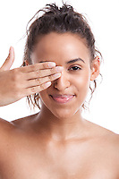 Portrait of young Mixed Race woman covering her eye with hand against white background