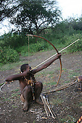 Africa, Tanzania, Lake Eyasi, Hadza man aiming arrow at a bird during a hunting expedition. Small tribe of hunter gatherers AKA Hadzabe Tribe April 2006