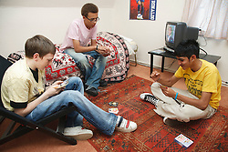 Group of youths in a bedroom playing cards.