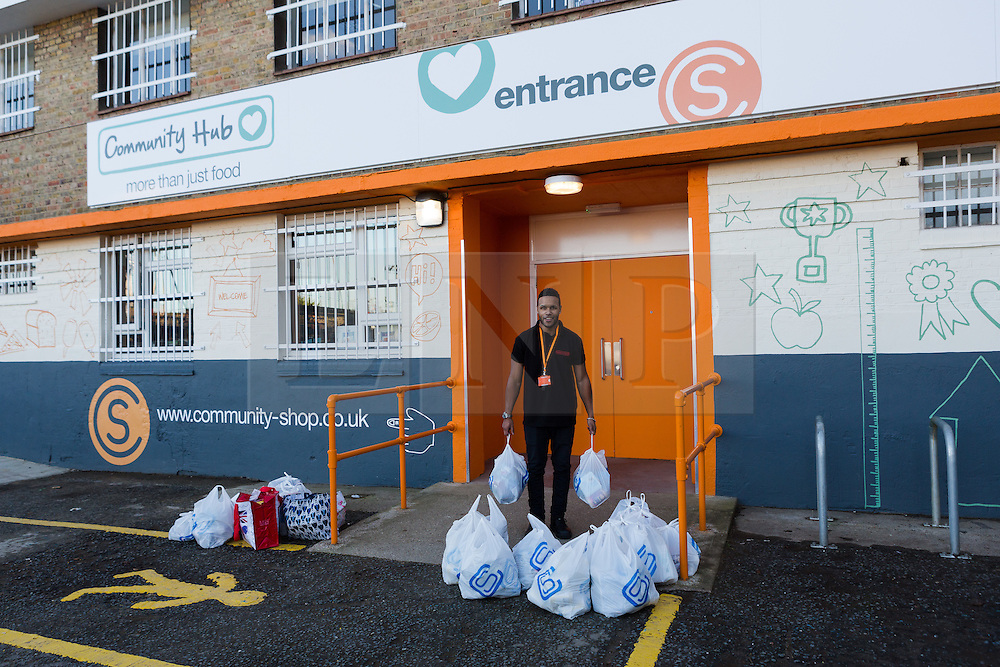 """© Licensed to London News Pictures. 19/12/2014. London, UK. A member of staff brings filled shopping bags for a customer ouside the Community Shop. The Community Shop opened this week in Gipsy Hill, South London and is a """"social supermarket"""", which sells heavily-discounted surplus food that would otherwise be thrown away. Food is received from retail brands such as Marks & Spencer, Asda, Tesco, Innocent and Muller and many more. The shop works on a membership basis only, serving residents who are on income support and aimed at people who are in work, but low waged and for those working hard to find a job. Photo credit : Vickie Flores/LNP"""