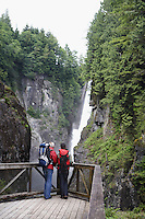 Man and woman watching waterfall back view