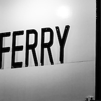 Panoramic photo of the Auto Ferry Sign to Balboa Peninsula in Newport Beach California in black and white. The Balboa Island Ferry transports people and cars across Newport Harbor between Balboa Island and Balboa Peninsula. Panorama ratio is 1:3.