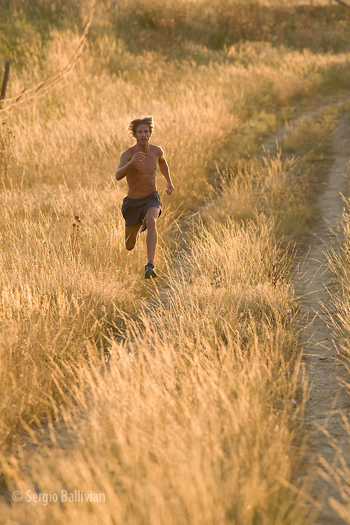 A man trail-running in the late afternoon through the Front Range of Colorado