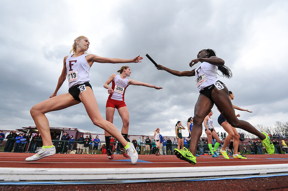AMHERST, MA - MAY 4: Kristen Stuart of Fordham University prepares to get the baton from Titi Fagade of Fordham University during the women's 4x800 meter relay on Day 2 of the Atlantic 10 Outdoor Track and Field Championships at the University of Massachusetts Amherst Track and Field Complex on May 4, 2014 in Amherst, Massachusetts. (Photo by Daniel Petty/Atlantic 10)