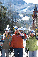 A group of skiers walks through Whistler Village on a sunny winter day.