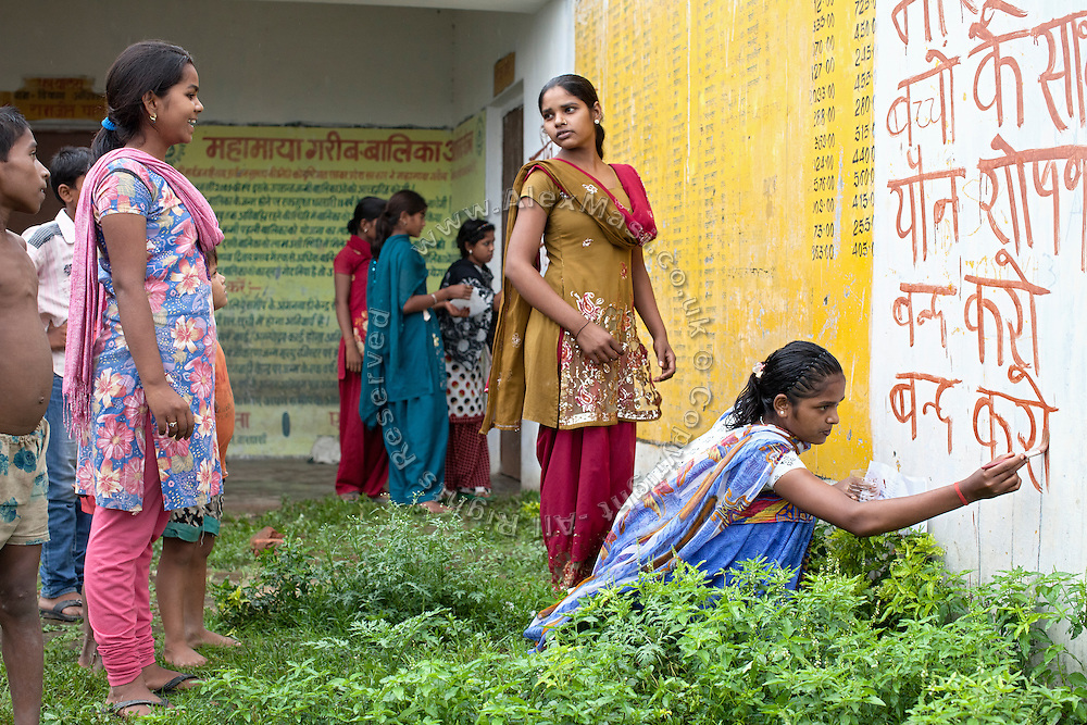 Young women are taking part to an awareness workshop organised by Neeta Shani, from the charity PVCHR, in Parmandapur, a rural area near Varanasi, Uttar Pradesh, India. The girls are painting pro-women slogans on the walls of the local Panchayat, or village council.