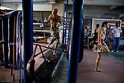"""Shuki (left) looks on as Gili (3rd from right) warms up in Rompo Muay Thai Gym, Khlong Toei, Bangkok city, Thailand on 14th December 2009..Shuki Rosenzweig, aged 40, is a professional Muay Thai Boxing fighter (champion) and trainer who has lived for 9 years in Thailand. He is famous in Israel as the authority of this sport. Started at the age of 12 in boxing in Israel, Jerusalem. Used to work in the fish market. His father is a 'legend' in Jerusalem fish market. Shuki stopped working with his dad about 13 years ago. He has opened some muay thai gyms in Thailand in the past. He currently has about 5 Israeli fighters under his training in Bangkok, besides fighters of other nationalities. Shuki found religion in Bangkok with Chabad about 4 years ago. He never misses Shabbat and loves to sing the songs of prayer, priding himself with a good voice. """"Chabad integrates all Jews. it keeps us together. When at Chabad, we are at home, united with people of the same culture, language and beliefs""""..Gil Saat (known affectionately as Gili), aged 29, from Ramat Gan, Israel, has been a boxer for 9 years. He is on his second trip to Thailand for muay thai. On the first trip, he stayed for 6 months, fighting in about 10 competitions in Thailand and once in Cambodia. Gili has graduated in many sport related courses from institutes in Thailand and Israel, including a diploma in Thai massage. He first met Shuki in Israel many years ago at a competition when Shuki was the trainer for Gili's opponent in the ring. A few years after that, Gili attended a seminar given by Shuki about muay thai and then decided to come to Thailand to train under him. Gili comes from a more religious family in comparison to Shuki. Gili's grand father is a rabbi in Israel. Gili introduced Shuki to Chabad (both Khao San and Sukhumvit) about 4-5 years ago and they have since spent every shabbat at Chabad. On 4th Dec 2009, they both turned up for shabbat immediately after a competition, still bleeding and Shuki wi"""