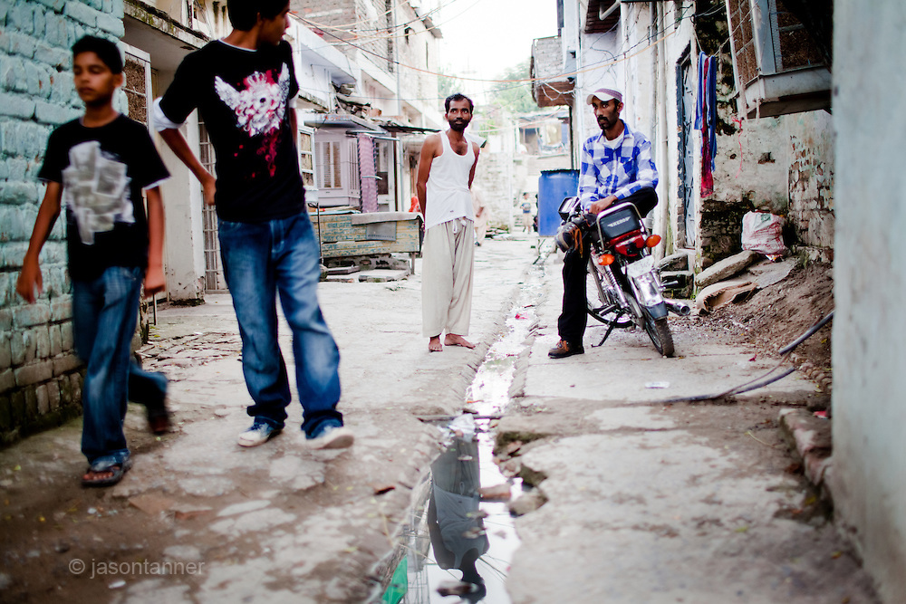 Islamabad: Young, unemployed men chat on one of the narrow alleyways of a Christian colony in Islamabad...Pakistan's Christian communities account for an estimated one percent of the country's 180 million population...I the middle of Islamabad's wealthiest neighbourhood is a 'colony' that's home to some 4000 Christians. Narrow alleys separate multi-storey, squalid houses with open sewers running meandering the alleys to the river that runs through the heart of the colony...Some are recent arrivals from Faisalabad and Gojra, where recent sectarian killings forced many to relocate to the relative safety of the capitol territory. Many are second and third generation residents squatting on land that sees no development assistance from the Capital Development Authority. Power outages are frequent, many residents sleep on the roofs during the long summer months, there are no air-conditioners in the colony...Many of the residents are unemployed; those fortunate to have any income usually work as servants, gardeners, drivers, security guards or cleaners. ..Discrimination against the Christian minorities is rampant in Pakistani society. Many suspect the government of deliberately keeping them at the bottom of the economic ladder to appease the radical religious parties...©JTanner/August2011