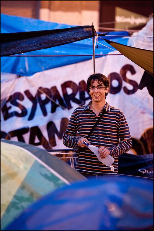 """Robin originaire de Lyon et sympathisant du mouvement de la puerta del Sol est venu pour le week end, il dort sur place et se rend utile la journee. // Le mouvement spontane du """"15 M"""" (15 mai) compose de citoyens espagnols campe depuis 2 semaines sur la place Puerta Del Sol avec pour revendication la construction d'une democratie nouvelle. Organise en commission les citoyens prennent la parole lors d'assemblee ouverte a tous - Place Puerta Del Sol à Madrid le Juin 2011. ©Benjamin Girette/IP3Press"""
