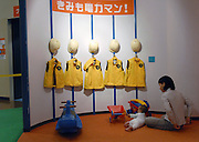 (FILE) A woman and young child play in front of a row of uniforms above which is a sign inviting young children to dress up as nuclear power plant workers at Hamaoka Nuclear Power Plant in Omaezaki, Shizuoka Prefecture, Japan in 2007. The subject of much controversy, the Hamaoka nuclear facility is built directly over the subduction zone near the junction of two tectonic plates. Photographer: Robert Gilhooly