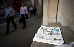 © London News Pictures. 01/07/2013. London, UK. Office workers walk past copies of 'City AM' with a front page report on the new governor of the Bank of England Mark Carney on July 01, 2013. The Bank of England is due to release the Money and Credit report for May. Photo credit: Ben Cawthra/LNP
