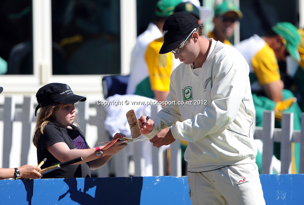Doug Bracewell signs autographs on Day 3 of the first test match between South Africa and New Zealand at the University Oval in Dunedin, New Zealand on Friday 9 March 2012. Photo: Andrew Cornaga/Photosport.co.nz