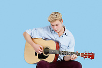 Young man playing guitar over blue background