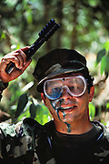 War game combatant at Sat Cong village paintball combat park near Los Angeles, California, USA. He surrenders after being shot in the face with a blue paintball. MODEL RELEASED.