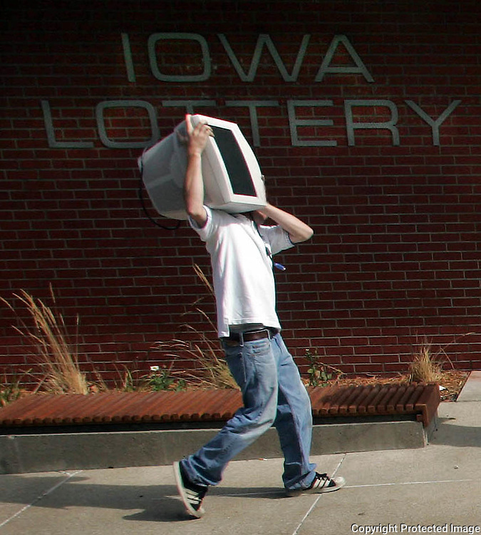 A workers carries computers into the the new headquarters for the Iowa Lottery, formerly the Farmers  Mutual Hail Insurance building at 2323 Grand Ave.  The relocation is just a few blocks from their former site.  photo by david peterson