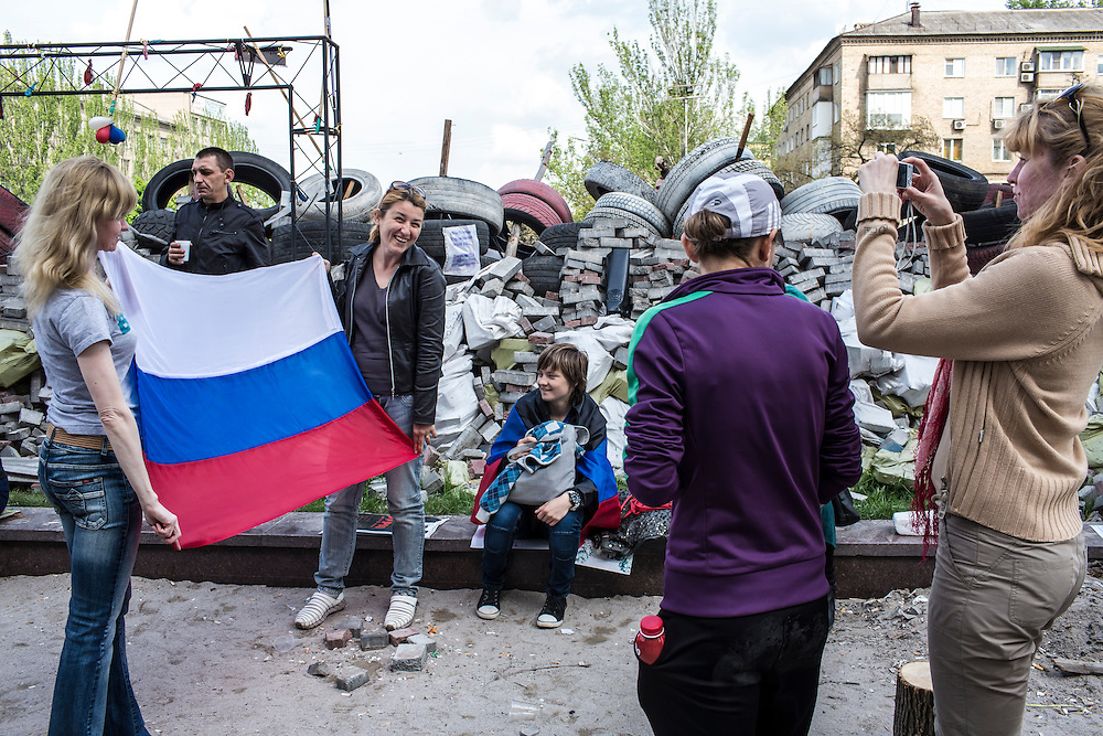 DONETSK, UKRAINE - MAY 4: Women pose for a picture with a Russian flag outside the regional administration building, which is occupied by pro-Russian protesters, on May 4, 2014 in Donetsk, Ukraine. Cities across Eastern Ukraine have been overtaken by pro-Russian protesters in recent weeks, leading the Ukrainian military to respond with force in some areas. (Photo by Brendan Hoffman for The Washington Post)