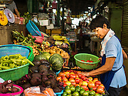 14 DECEMBER 2015 - BANGKOK, THAILAND:   A woman looks for tomatoes in a shop in Bang Chak Market. The market closes permanently on Dec 31, 2015. The Bang Chak Market serves the community around Sois 91-97 on Sukhumvit Road in the Bangkok suburbs. About half of the market has been torn down. Bangkok city authorities put up notices in late November that the market would be closed by January 1, 2016 and redevelopment would start shortly after that. Market vendors said condominiums are being built on the land.     PHOTO BY JACK KURTZ