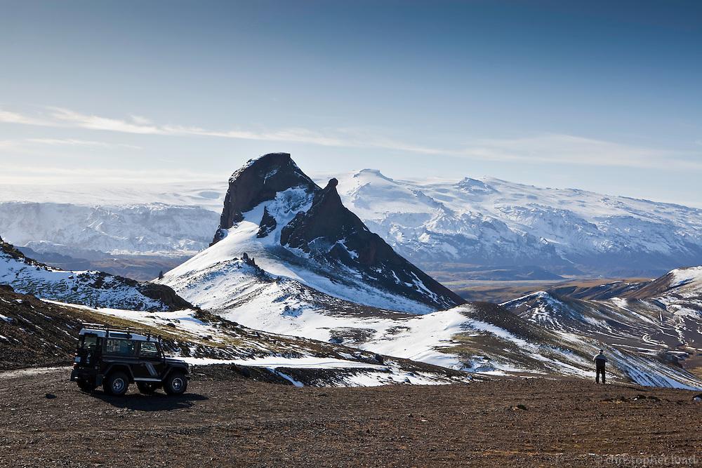 A Land Rover Defender by mountain Einhyrningur. A man admiring the view. Glacier Eyjafjallajokull in background.<br /> <br /> Land Rover Defender við fjallið Einhyrning. Ferðamaður virðir fyrir sér útsýnið. Eyjafjallajökull í baksýn.