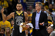 June 3, 2018; Oakland, CA, USA; Golden State Warriors head coach Steve Kerr and guard Stephen Curry (30) react to a play during the second quarter against the Cleveland Cavaliers in game two of the 2018 NBA Finals at Oracle Arena.