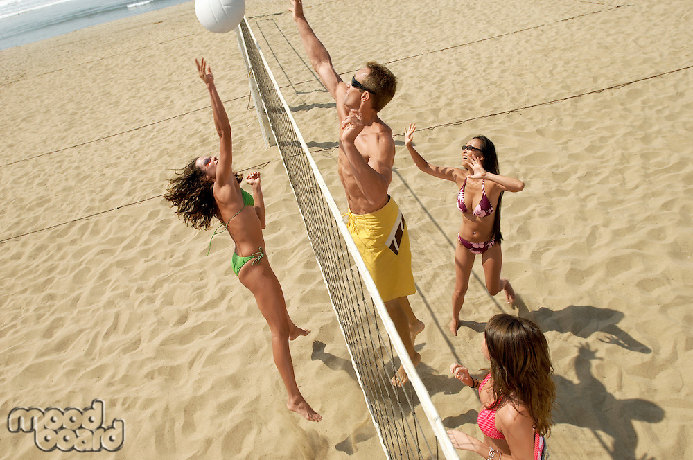 Small group of young people playing volleyball on sandy beach