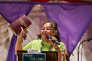 "12 JULY 2012 - FT DEFIANCE, AZ: FLORENCE BARKER, from the Manuelito Church of God, holds up a Navajo Bible while she preaches at the 23rd annual Navajo Nation Camp Meeting in Ft. Defiance, north of Window Rock, AZ, on the Navajo reservation. Preachers from across the Navajo Nation, and the western US, come to Navajo Nation Camp Meeting to preach an evangelical form of Christianity. Evangelical Christians make up a growing part of the reservation - there are now more than a hundred camp meetings and tent revivals on the reservation every year. The camp meeting in Ft. Defiance draws nearly 200 people each night of its six day run. Many of the attendees convert to evangelical Christianity from traditional Navajo beliefs, Catholicism or Mormonism. ""Camp meetings"" are a form of Protestant Christian religious services originating in Britain and once common in rural parts of the United States. People would travel a great distance to a particular site to camp out, listen to itinerant preachers, and pray. This suited the rural life, before cars and highways were common, because rural areas often lacked traditional churches.      PHOTO BY JACK KURTZ"